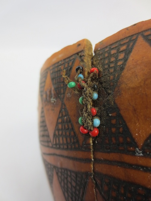 gourd vessel with visible mending using beads