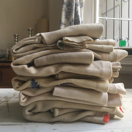 a pile of tomofholland repaired cardigans for wolf and gypsy